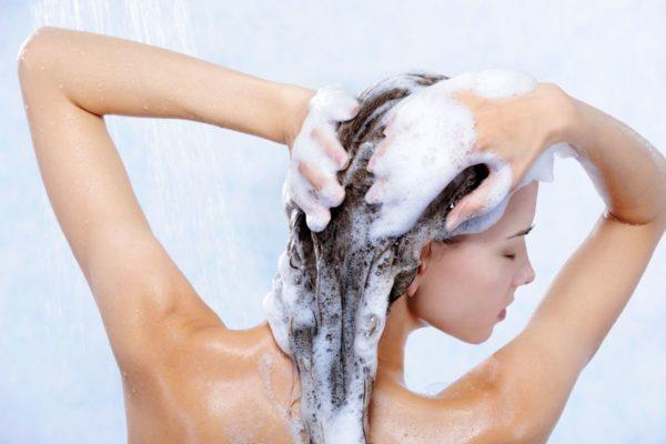 Девушка моет голову шампунем, как выбрать шампунь
