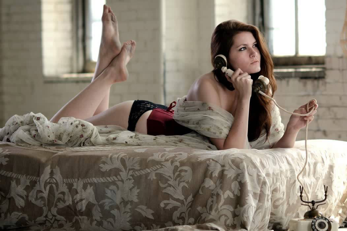 Девушка лежит на кровати и говорит по телефону